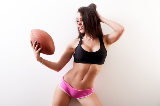 Dark haired young woman fitness model in black sports top, pink shorts holding a rugby ball and posing on white isolated background
