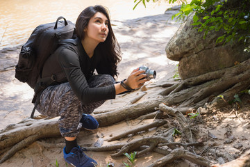 Asian woman backpack taking a photo with mirrorless camera