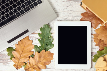 Gray notebook. Autumn leaves. Modern tablet