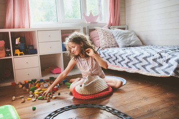 child girl cleaning her room and organize wooden toys into knitted storage bag. Housework and help concept