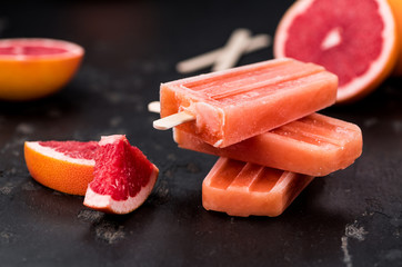 Slate slab with fresh Grapefruit Popsicles (selective focus)