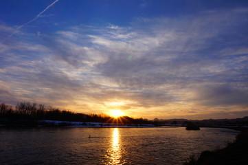 川の日没 青空 太陽の光芒