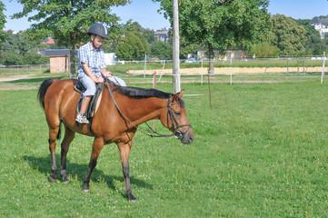 ein 9 jähriger Junge reitet allein auf dem Reitpaltz auf einem braunem Pferd