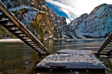 Braies lake framed by the stairs of the mountain lake boat shelter