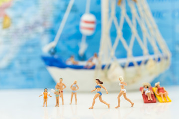Miniature people : Families running on the beach happily. Have a boat as a backdrop, used as a business travel concept.