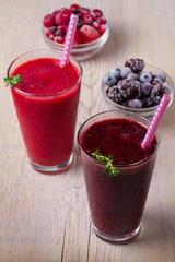 Frozen summer berries smoothie: blueberries, strawberries, raspberries, cranberries, currants and blackberries on wooden background, vertical