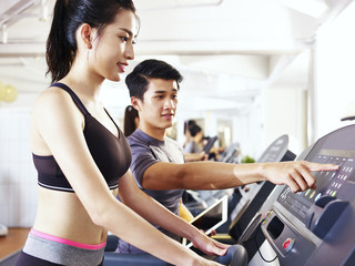 young asian adult woman exercising on treadmill helped by trainer