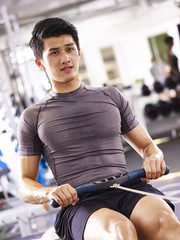 asian young man working out on rowing machine
