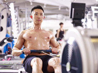 young asian man working out using rowing machine