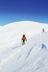 Winter hike in the mountains with a backpack and tent.