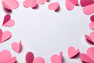 Beautiful pink paper hearts on white paper background