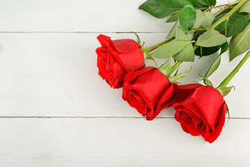 Beautiful red roses on a white wooden background. Flat lay, top view.