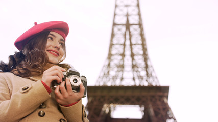 Creative girl holding camera in hands, enjoying photography hobby in Paris