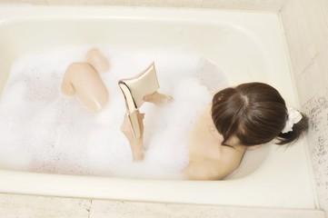 入浴しながら本を読む女性