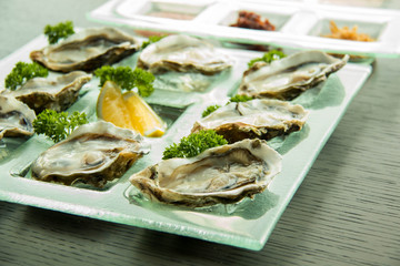 Oysters on glass plate with spicy sauce