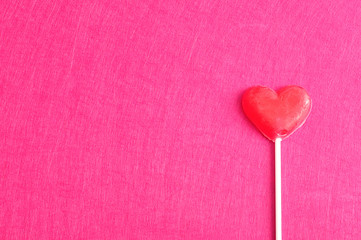 Valentines day. A red heart shape lollipop isolated against a pink background
