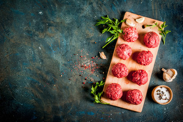 Raw meatballs with olive oil and spices on dark concrete table, top view copy space