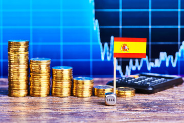 Downtrend of stacks of gold coins, flag of Spain, dice cube and calculator