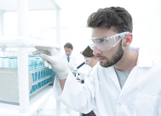 A young man doing an experiment in a chemical laboratory