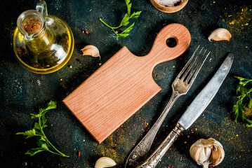 Cooking food concept, spices, herb and oil for preparing dinner, with cutting board, table knife and fork, copy space top view