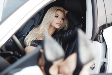 Young woman driving a car in the city.Successful, attractive, beautiful, young woman - blonde, sitting at the wheel of an expensive car. Portrait of a beautiful woman in a car