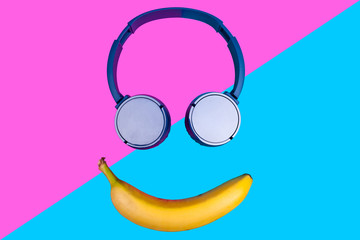 Pop art flat concept of banana and headphones on vivid colored background forming a smile face....
