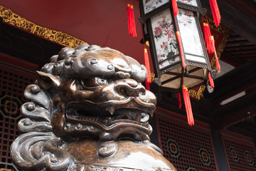 Lion bronze statue in front of a buddhist temple in China