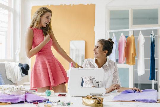 Two happy young women in fashion studio