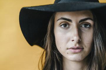 Portrait of brunette young woman wearing a floppy hat