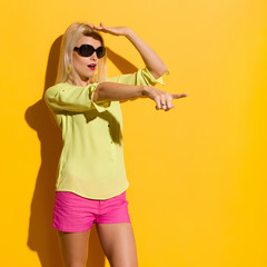 Beautiful Blond Woman In Sunglasses Is Pointing And Looking Away