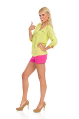 Smiling Beautiful Blond Woman In Vibrant Clothes And High Hells Is Standing And Showing Thumb Up