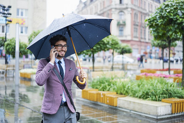Fashionable businessman on the phone on rainy day in the city