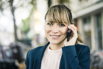 Portrait of smiling businesswoman on cell phone outdoors