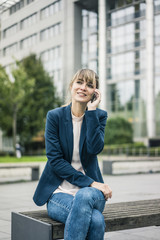 Smiling businesswoman sitting on bench talking on cell phone outdoors