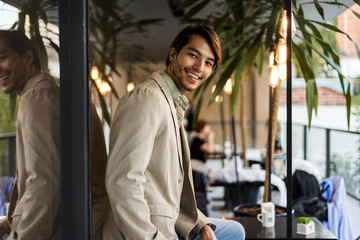 Portrait of smiling young man at an outdoor cafe