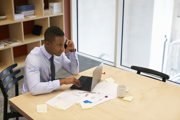 Young black man using smartphone in a boardroom, elevated view