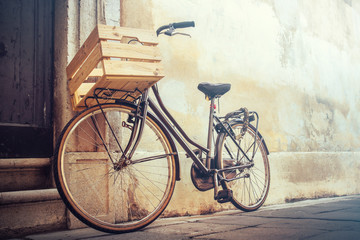 Foto op Plexiglas Fiets vintage bicycle with copy space, bike with wooden basket standing on a wall