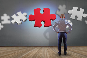 Businessman in front of a wall with Puzzle pieces