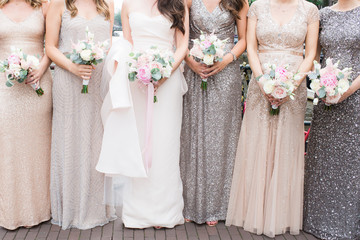 bride and bridesmaids holding pastel bouquets
