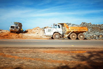 parked yellow quarry tipping truck on the road near construction works