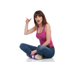 Surprised Young Woman In Magenta Tank Top Is Pointing