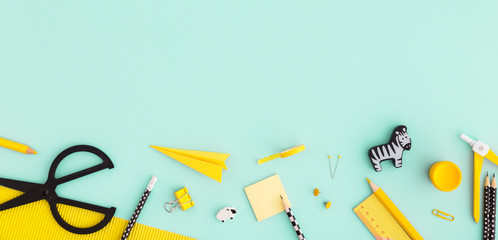 School or office workspace with yellow supplies on cyan background. Flat lay.