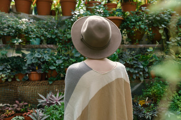 Fashionable young woman wearing in hat and poncho among tropical plants.