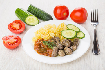 Fried chicken hearts, pasta, baked eggplants, cucumbers, tomatoes and fork