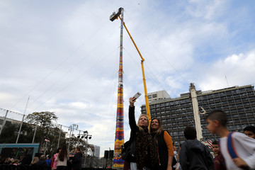 Women pose for a selfie next to a 36-meter (118 feet) tower built in an attempt to break the Guinness world record for the highest building blocks structure in Tel Aviv