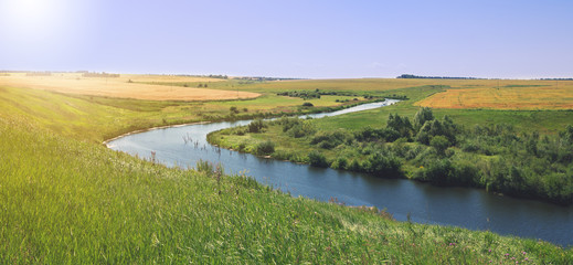 Sunny summer landscape with river.Green hills and meadows.Fields of ripe wheat.