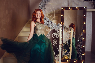 Beautiful woman in luxurious dress has found a gift under the Christmas tree