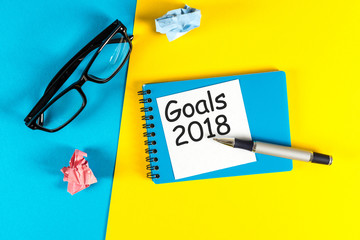 New year goal, text on notepad with office accessories. Business motivation, inspiration concepts. 2018 Goals