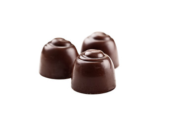 Three chocolate covered cherries isolated over white background with clipping path included. Shallow depth of field with selective focus on candy in foreground.