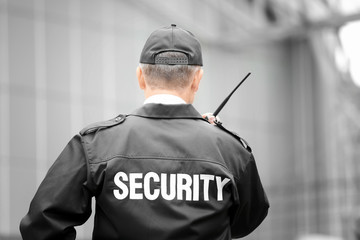 Male security guard using portable radio outdoors Wall mural